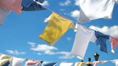 A lot of t-shirts are dried in the Sun rope Stock Footage