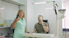 Man having her eyes examined by an eye doctor Stock Footage