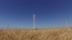 Eolic turbine wind renewable energy farm in wheat field steady shot 4k Stock Footage