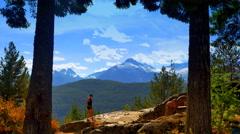 4K Hiking Woman Silhouette on Ridge, Twin Fir Trees Mountain Range Background Stock Footage