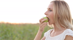 Caucasian woman with a toothpain sitting on a park bench and eating green apple Stock Footage