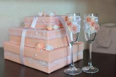Two fancy wedding glasses with decorated box on background. Carrot color Stock Photos