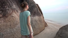 Young woman with hair in a bun walks on the beach. Slow motion Stock Footage