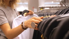 Female Customer Shopping for Clothes in Clothing Store Stock Footage