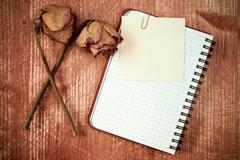 Old roses and notebook with sticky note Stock Photos