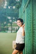 Asian female relax and smile standing on tennis court and looking at camera Stock Photos