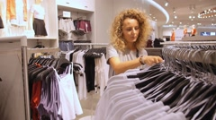 Woman Customer Choosing Clothes in Shopping Mall Arkistovideo