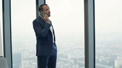 Young businessman talking on cellphone by window in the office Stock Footage