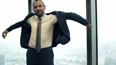 Portrait of happy businessman dressing up suit jacket in the office Stock Footage