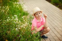 Boy sitting in the flowers in the spring time Stock Photos