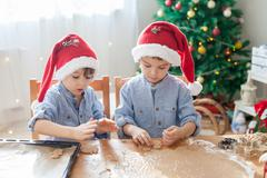 Two cute boys with santa hat, preparing cookies at home, Christmas tree Stock Photos