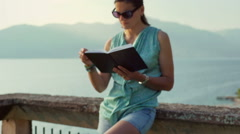 Absorbed woman standing next to the sea and reading something, steadycam shot Stock Footage