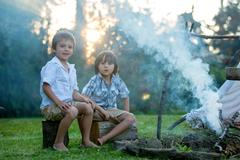 Two sweet children, boy brothers, camping outside summertime on sunset Stock Photos