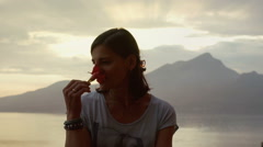 Happy woman standing with the flower next to the sea and smiling to the camera Stock Footage