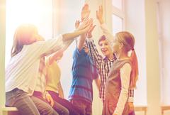 Group of smiling school kids making high five Stock Photos
