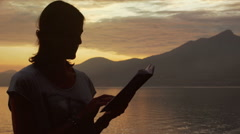 Woman reading publication while standing next to the seaside at sunset Stock Footage