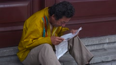 A Cuban man reads a newspaper on the streets of Havana. Stock Footage