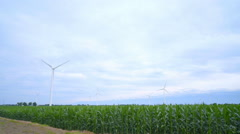 Wind turbines stand in green field. Green energy and renewable power Stock Footage