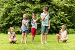 Kids with smartphones playing game in summer park Stock Photos