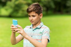 Boy with smartphone playing game in summer park Stock Photos
