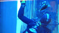 Scuba diver washing big water tank glass from inside. Environment care concept Stock Footage