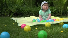 Healthy baby spent time between colorful balls on plaid in meadow. 4K Stock Footage