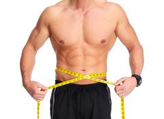 Man abdomen with measuring tape over blue background. Stock Photos