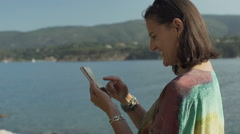 Happy woman standing next to the water and browsing interne on smartphone Stock Footage
