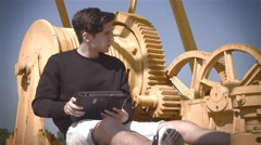 Young man with tablet in front of industrial gears Stock Footage