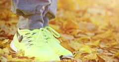 Tying laces on Running shoes in Autumn. 4K DCi SLOW MOTION 120 fps. Lens Flare Stock Footage