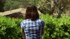 Woman walking on switchback next to the bushes while sun shining Stock Footage