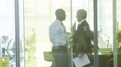 Two businessmen meet and shake hands in modern city office Stock Footage
