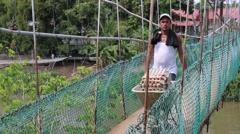 Panamanian local pushing a wheelbarrow full of eggs across shaky bridge Stock Footage