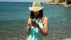 Attractive woman smiling to the camera while standing next to the sea, steadycam Stock Footage