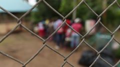 Rack Focus Through Chain Link Fence of Cuban Migrants in Compound Stock Footage