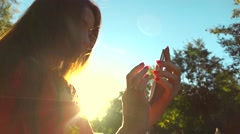 Beautiful girl in red dress using her mobile phone in the park, warm sunset Stock Footage