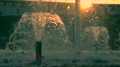 Super slow motion shot of a beautiful park fountain against sunset, orange sun Stock Footage