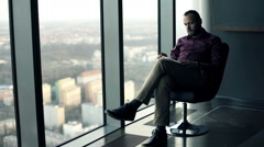 Young man reading book sitting on armchair with splendid city view Stock Footage