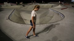Blonde Girl Does Handstand in Foreground of Skateboarder in Pool Stock Footage