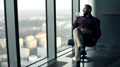 Young, happy man drinking wine on armchair with splendid city view Stock Footage