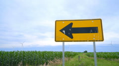 Road sign pointing to wing turbines farm. Farm field with wind turbines Stock Footage