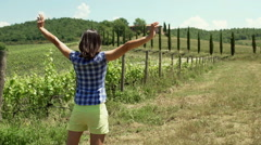 Woman standing on the grassland and holding her hands up, steadycam shot Stock Footage