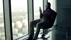 Young, happy man sitting with smartphone on armchair with splendit city view Stock Footage