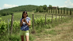 Happy woman receiving good news on smartphone while standing on the field, stead Stock Footage