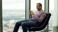 Young man playing game on smartphone while sitting on armchair with city view Stock Footage