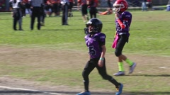 Two Peewee Football Players Return to Sideline Stock Footage
