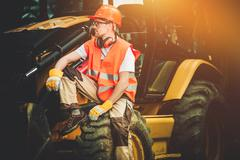 Bulldozer Construction Worker Resting on His Heavy Duty Machinery. Stock Photos