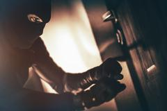Caucasian House Burglar in Action. House Burglary Concept Photo. Home Safety Stock Photos