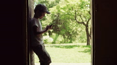 Boy standing in the doors with the view on garden and using smartphone, steadyca Stock Footage