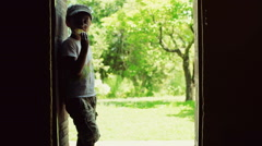 Boy standing in the doors with the view on garden and eating snack, steadycam sh Stock Footage